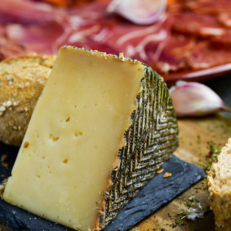 closeup of a piece of manchego cheese, and a plate with an assortment of different spanish cold meats as chorizo, cured pork tenderloin and serrano ham in the background
