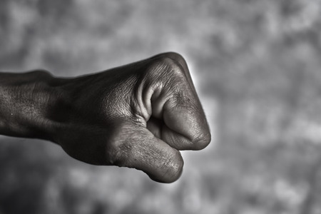 closeup of the fist of a young caucasian man in the air ready to punch or fight, against a graded gray background, with a dramatic effect