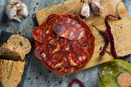 high-angle shot of an earthenware plate with some slices of spanish chorizo, cured pork sausage, some slices of bread, a glass cruet with olive oil and some garlics, on a rustic gray wooden table Stock Photo