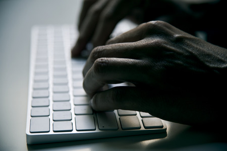 cyberwarfare: closeup of a young man typing in a computer keyboard in gloom, with a dramatic effect