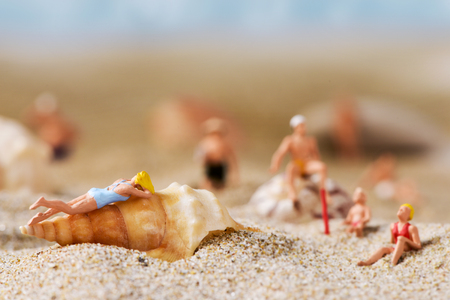 bather: some different miniature people wearing swimsuit relaxing on the sand of the beach