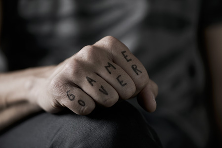 terminating: closeup of the hand of a young caucasian man with the text game over written with a temporary ink in his knuckles, with a dramatic effect