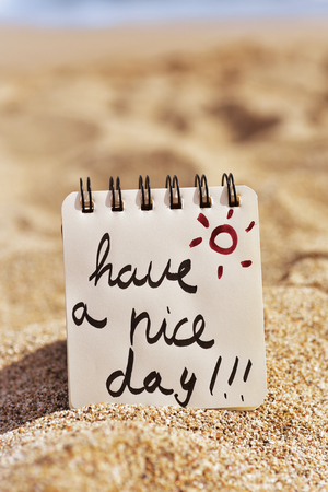closeup of a notepad with the text have a nice day written in it, placed on the sand of a beach