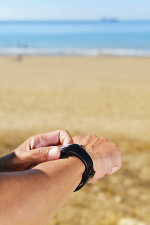 cronógrafo: closeup of a young sportsman syncing his smartwatch, with the sea in the background and a large blank space above him Foto de archivo