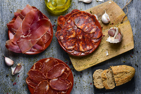 high-angle shot of some plates with an assortment of different spanish cold meats as chorizo, cured pork tenderloin and serrano ham, bread and a cruet with olive oil on a rustic gray table Stock Photo