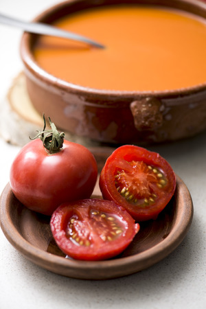 a rustic brown earthenware bowl with tomato soup and some tomatoes in a brown earthenware plate, on a white table