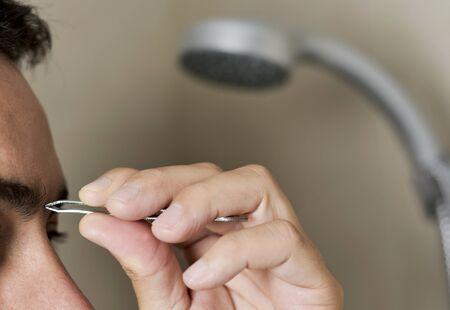 Close-up van een jonge Kaukasische man in de badkamer die zijn wenkbrauwen met pincet pikt