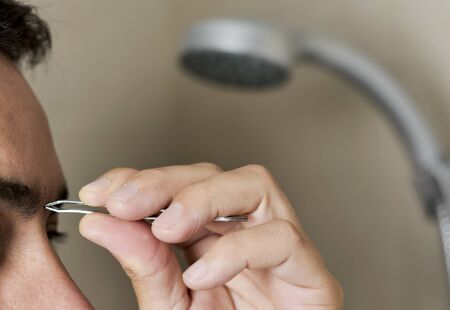 closeup of a young caucasian man in the bathroom plucking his eyebrows with tweezers Stock Photo