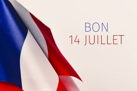 some french flags and the text text bon 14 juillet, happy 14 july, the national day of France written in French, against an off-white background Stock Photo