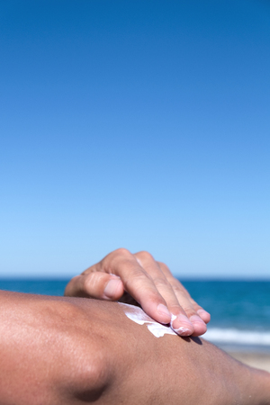 a bathing place: closeup of a young caucasian man on the beach man applying sunscreen to his arm, with a large blank space on top