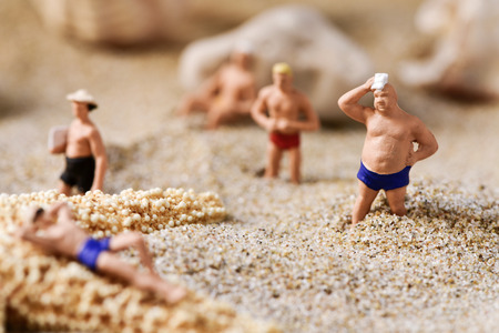 bather: some different miniature men wearing swimsuit relaxing next to some seashells and a starfish on the sand of the beach
