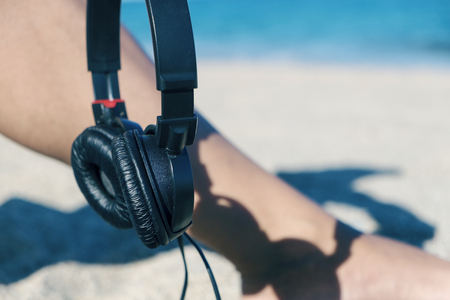 a bathing place: closeup of a young man holding a pair of headphones in his hand sitting in the sand of the beach