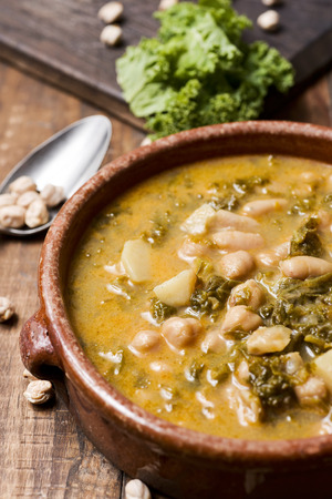 closeup of an earthenware bowl with kale stew with potatoes and chickpeas, on a rustic wooden table sprinkled with some dry chickpeas Stock Photo