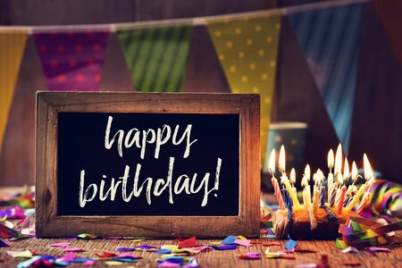 a wooden-framed chalkboard with the text birthday written in it, placed on a rustic wooden background sprinkled with confetti next to a cake with lit candles and a colorful garland in the background Фото со стока