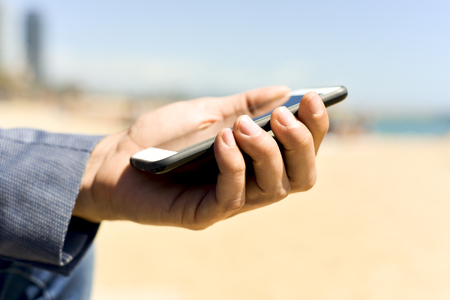 travelling salesman: closeup of a young caucasian man, wearing a smart casual look, a pair of jeans and an elegant blue jacket, using a smartphone next to the beach