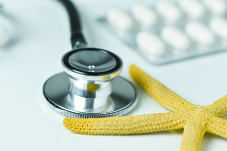closeup of a yellow starfish on a doctors office, next to a computer keyboard, a stethoscope and some pills, depicting the medical aid in summer concept