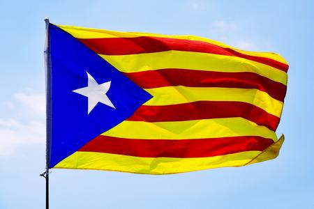 La estelada, la bandera catalana pro-independencia, ondeando en el cielo azul Foto de archivo - 82309862