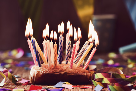 a small cake topped with some lit candles before blowing out the cake, on a rustic wooden table, sprinkled with confetti and a colorful garland in the background Stock Photo