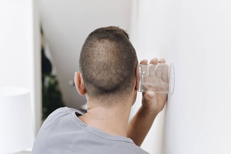 closeup of a young caucasian man seen from behind trying to hear through the wall with a glass
