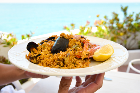closeup of a young man bringing a plate of typical spanish paella, with seafood, to a table set for lunch, with the sea in the background Stock Photo