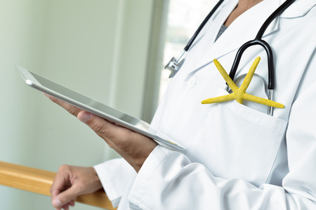 closeup of a young caucasian doctor man using a tablet with a colorful yellow starfish and a stethoscope in the pocket of his white coat, depicting the medical assistance in summer Stock Photo