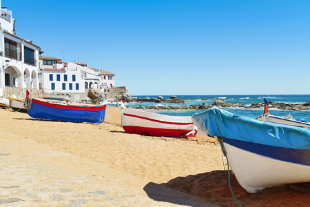 some old fishing boat stranded on the Barques Beach in Calella de Palafrugell, Costa Brava, Catalonia, Spain, with its characteristics white houses with portico in the background