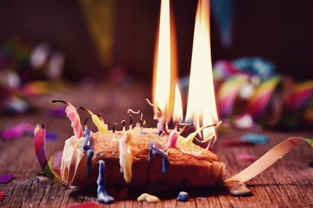 a small cake topped with some lit candles and some other unlit candles after blowing out the cake, on a rustic wooden table, sprinkled with confetti and a colorful garland in the background
