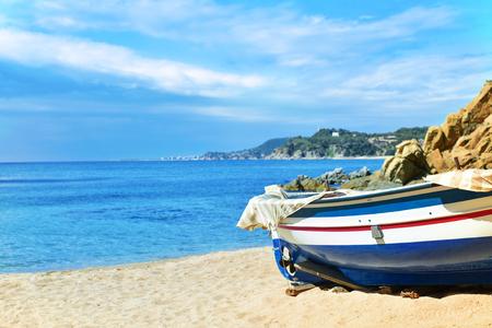 an old fishing boat stranded in the quiet beach Platja de Sa Caleta in Lloret de Mar, in the Costa Brava, Spain