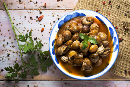 high-angle shot of a ceramic bowl with spanish caracoles en salsa, cooked snails in sauce, on a rustic wooden table Archivio Fotografico