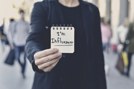 closeup of a young caucasian man in the street showing a spiral notepad with the text I am influencer written in it Stock Photo