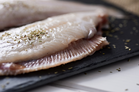closeup of a pair of raw filleted common sole on a slate tray placed on a rustic wooden table Stockfoto