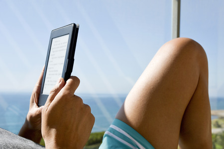 closeup of a young caucasian man wearing swimsuit reading in a tablet or e-reader in a balcony, with the ocean in the background Stock Photo