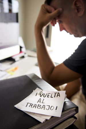 closeup of a concerned man sitting at his office desk and a note in the foreground with the text vuelta al trabajo, back to work written in spanish Stock Photo
