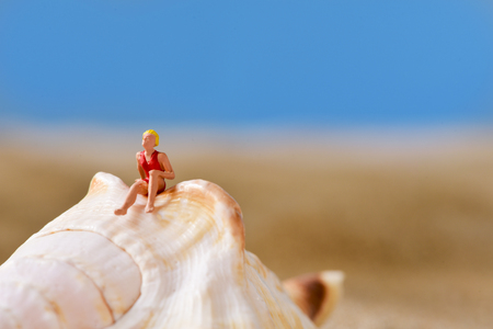 closeup of a miniature woman wearing swimsuit relaxing on a seashell on the beach, with a negative space on top Stock Photo