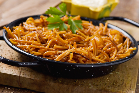 closeup of a spanish fideua, a typical noodles casserole with seafood, in a paella pan and aioli sauce in a yellow mortar on a rustic wooden table Stockfoto