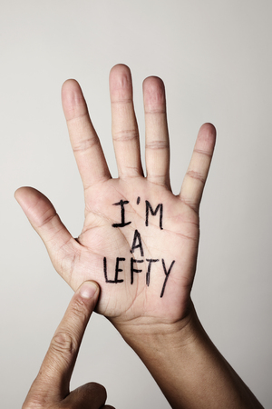 the text I am a lefty written in the palm of a left-handed man, against a beige background
