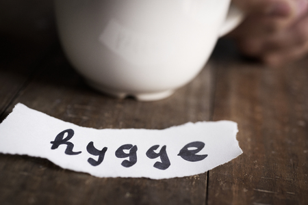closeup of a cup of coffee in the hand of a young man on a wooden table and a piece of paper with the text hygge, a danish and norwegian word for comfort or enjoy, a whole philosophy of life
