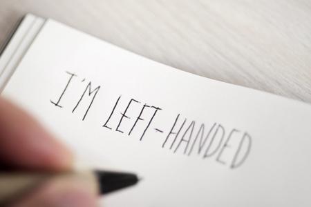 젊은 왼손잡이 남자 필기 텍스트의 근접 촬영 나는 메모장에서 왼쪽 손으로 테이블에 배치 스톡 콘텐츠