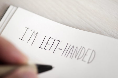 closeup of a young left-handed man handwriting the text I am left-handed in a notepad placed on a table Archivio Fotografico