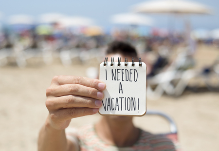 closeup of a young man in the beach showing a spiral notepad with the text I needed a vacation handwritten in the first page