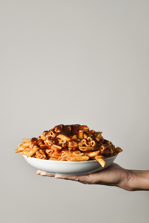 gastro: closeup of a young caucasian man holding a plate with an assortment of different cooked pasta served with tomato sauce in his hand, against an off-white background with a blank space on top Stock Photo