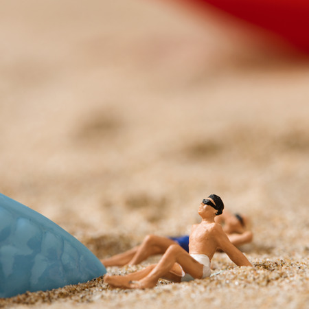 woman bath: miniature man and miniature woman wearing swimsuit relaxing next to a blue plastic starfish on the sand of the beach