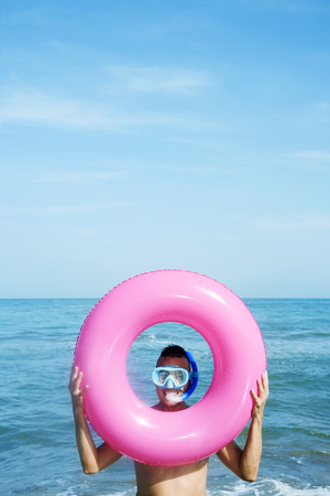 a bathing place: closeup of a young caucasian man wearing a diving mask and a snorkel popping up his face through the hole of a pink swim ring on the beach, with a negative space on top