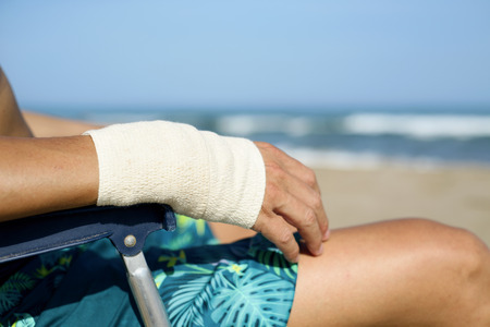 closeup of a young caucasian man in swimsuit sitting in a deck chair on the beach with a bandage in his wrist Stock Photo