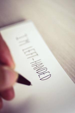 テーブルの上に置かれたメモ帳で左利き左きき若者手書きテキストのクローズ アップ