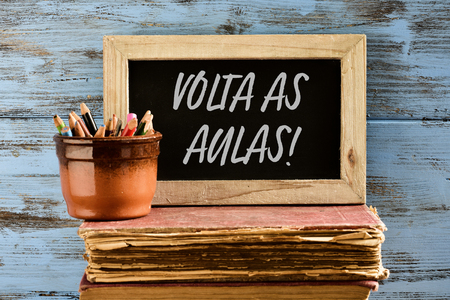 a wooden-framed chalkboard with the text volta as aulas, back to school in portuguese written in it, on a pile of old books next to an earthenware pot with pencil crayons