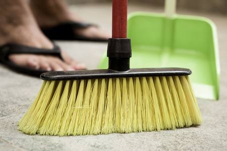 closeup of a young man sweeping the floor with a broom of green synthetic bristles and a green dustpan Stock Photo