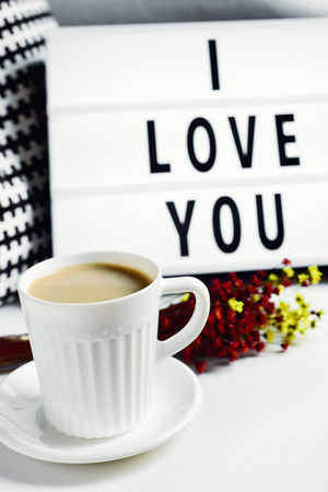 closeup of a white ceramic cup with coffee on a table, a bunch of flowers and a lightbox in the background with the text I love you written in it