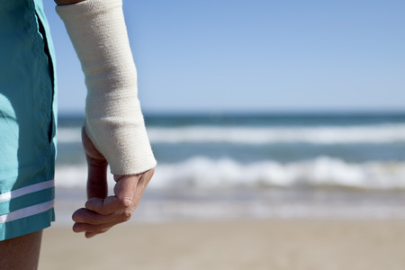 closeup of a young caucasian man in swimsuit on the beach with a bandage in his wrist, in front of the sea, with a negative space on the right Stockfoto