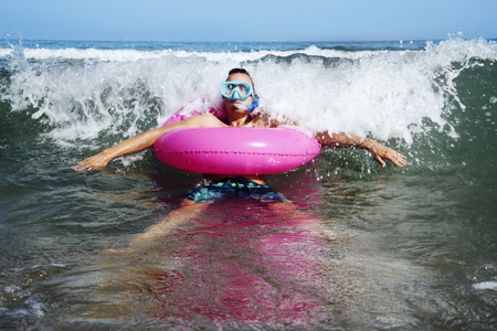 a young caucasian man wearing a diving mask, a snorkel and a pink swim ring into the seawater, next to the seashore Stock Photo
